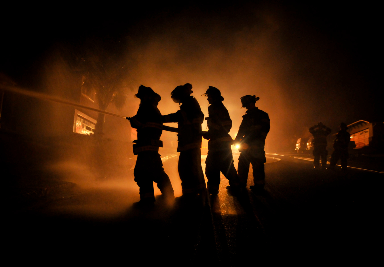 Firefighters aim a hose towards a burning house after a gas explosion