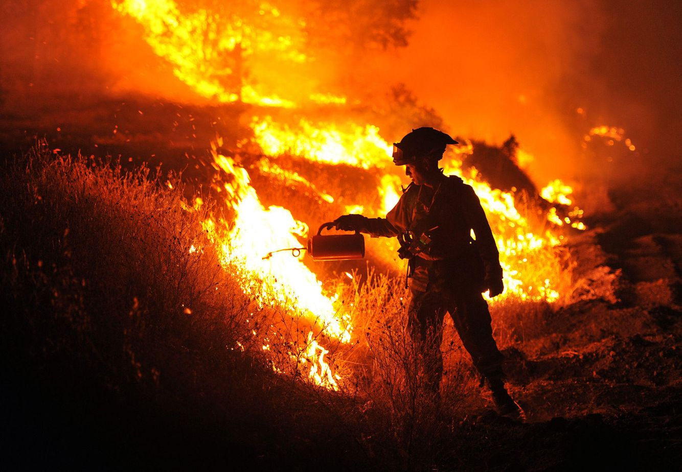 A firefighter lights a backburn