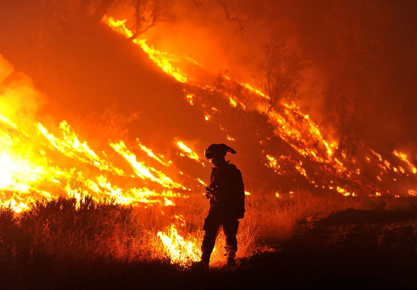 A firefighter pauses while surrounded by flames