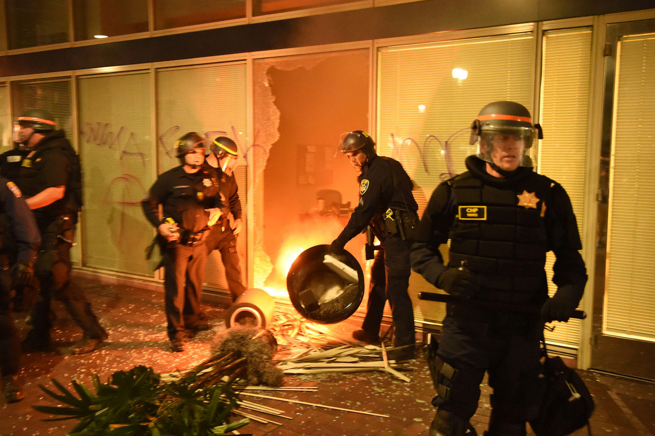 Police investigate a building firebombed during an anti-Trump protest.