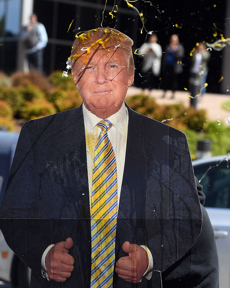 An egg is thrown at a cardboard cutout of Donald Trump during a protest where he was speaking in San Francisco.