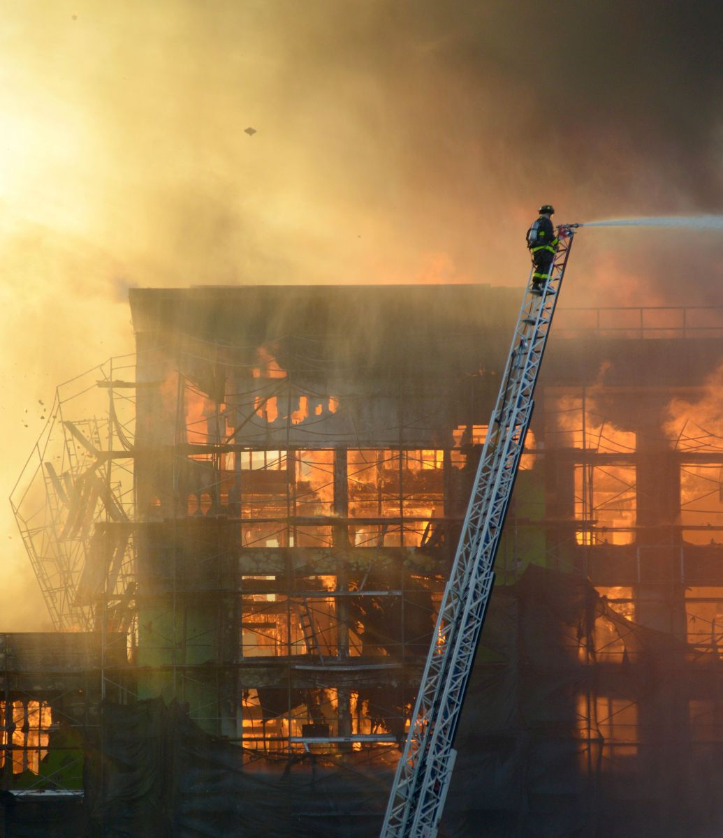 FIRE: A building crumbles as flames overtake a construction site in San Francisco.