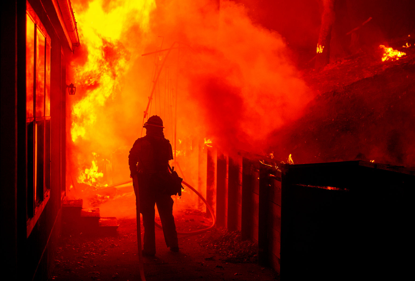 A firefighter attempts to save a burning home during the Valley fire.