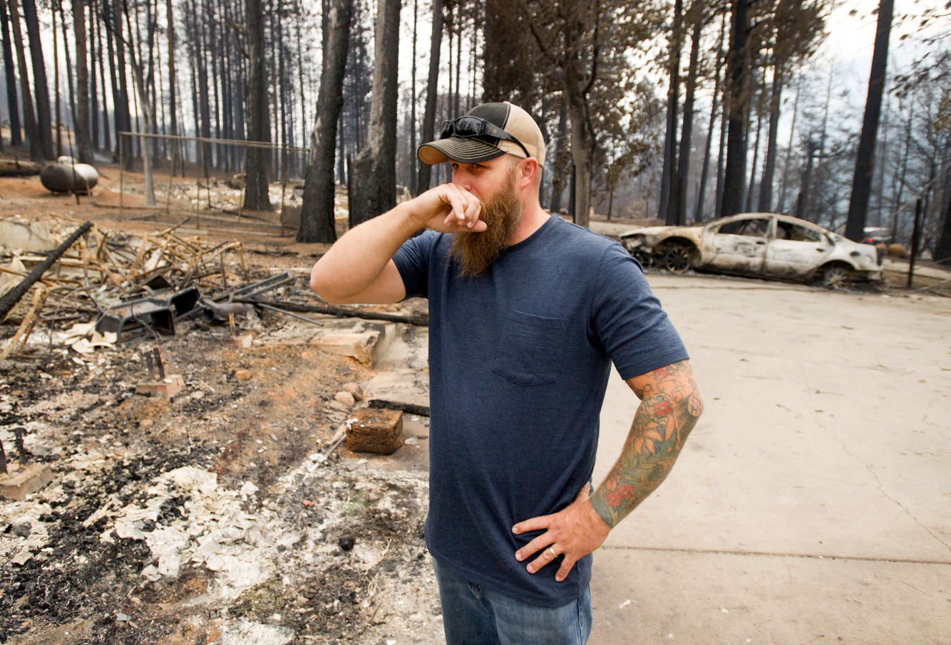 Josh Wood reacts while viewing the burned out remains of his home.