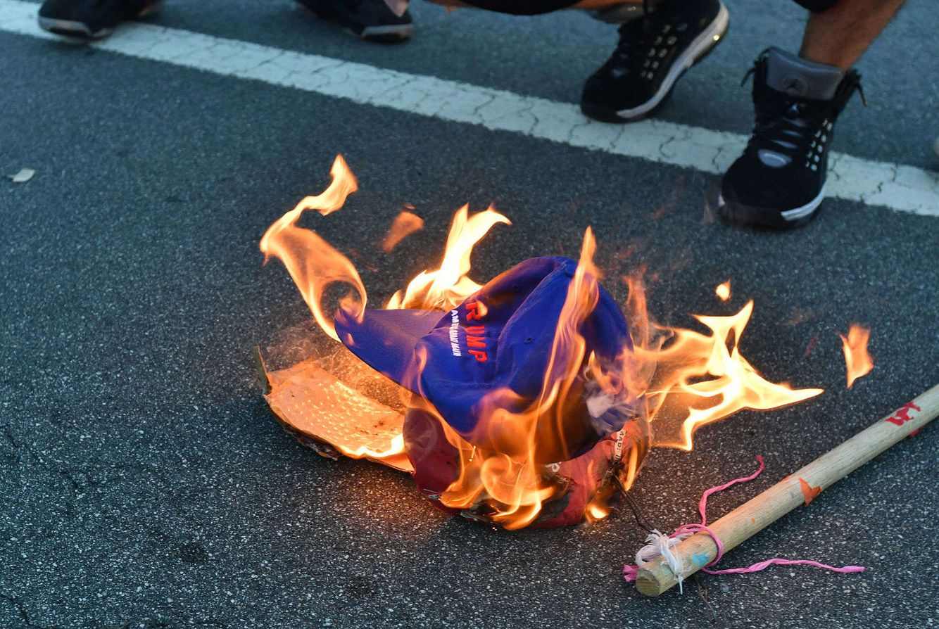 Protesters burn a Trump hat during a protest.