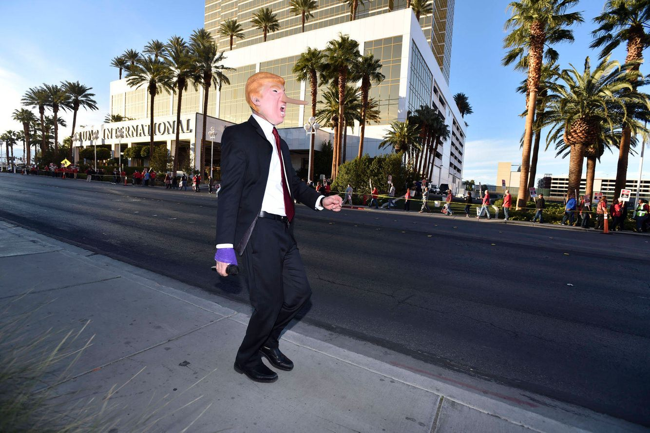 An anti-Trump protesters sings and dances in front of the Trump Hotel in Las Vegas.