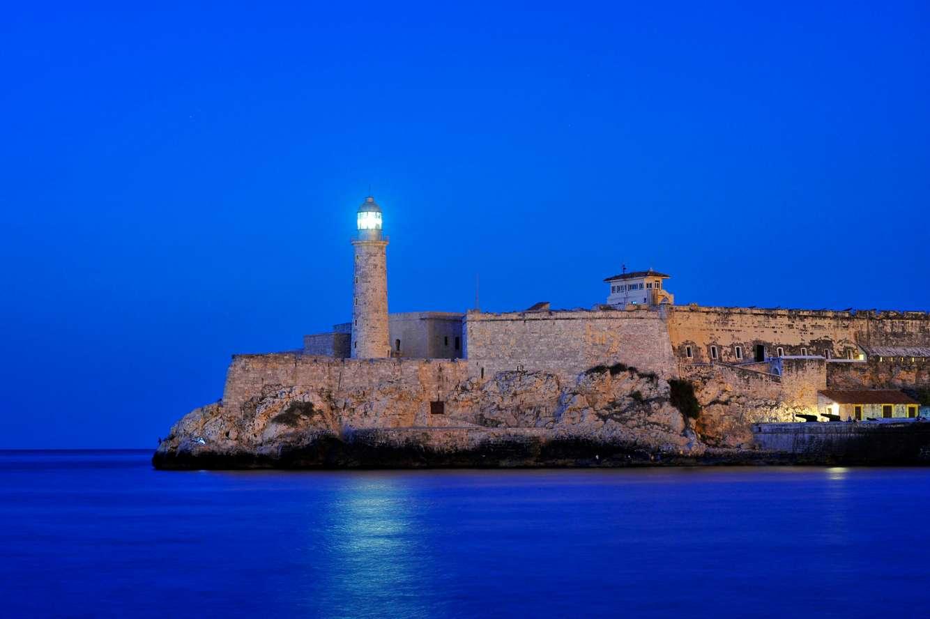 A Lighthouse shines at dusk in Havana, Cuba.