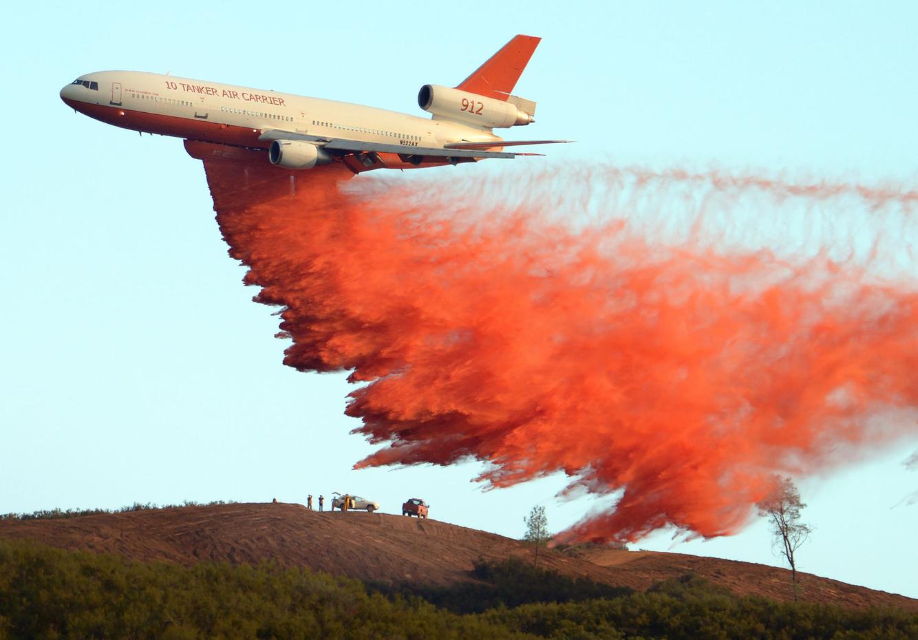 An air support tanker drops fire retardant on a ridge