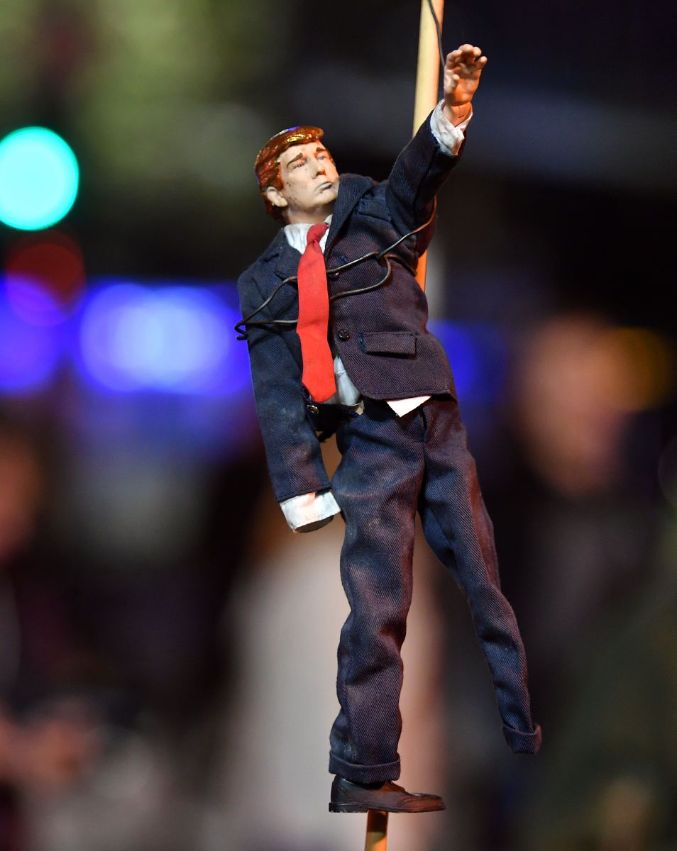 A Trump doll motioning like Hitler is held during a protest.