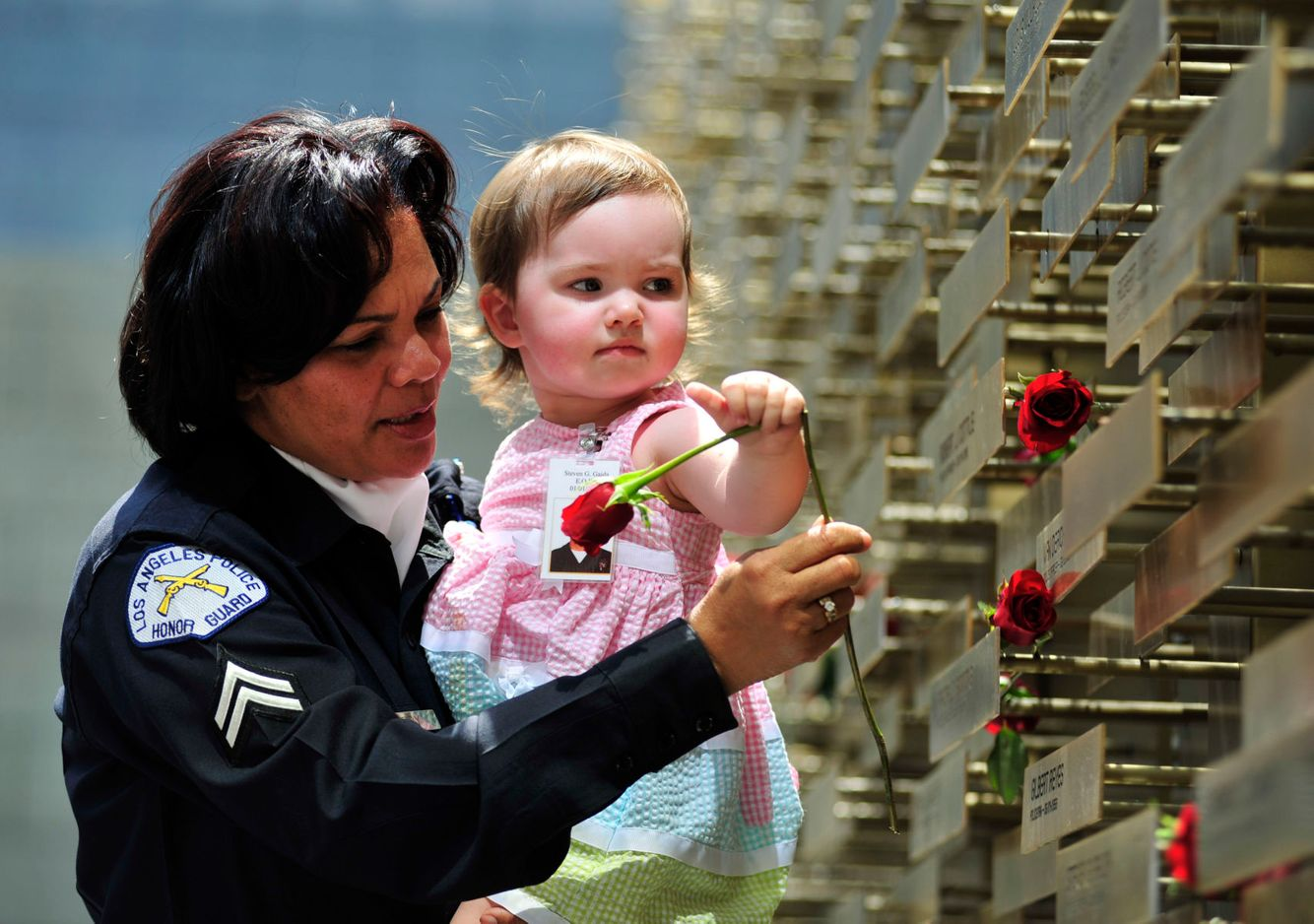 MEMORIAL: A member of th LAPD helps the niece of a fallen Officer place a rose at a memorial in Los Angeles