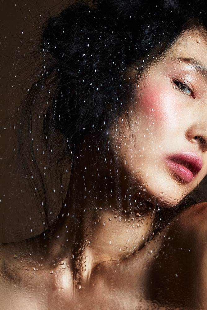Model photographed through glass that is covered with water drops. Makeup: Anthony Merante, Hair : Kristin Heitkotter Model: Dinara Ratchetyrova represented by HMMLA