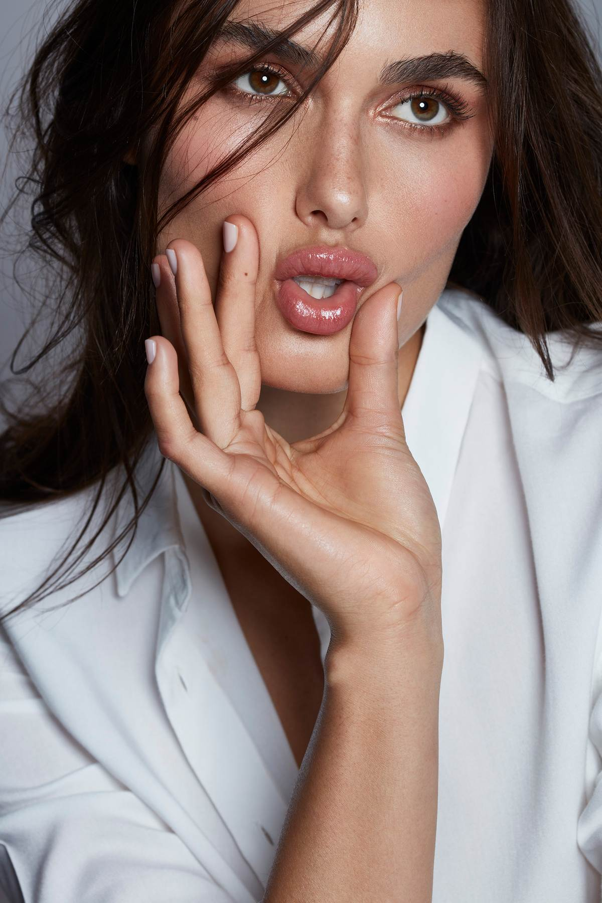 close up of a model with a fresh glowing skin and making a funny face