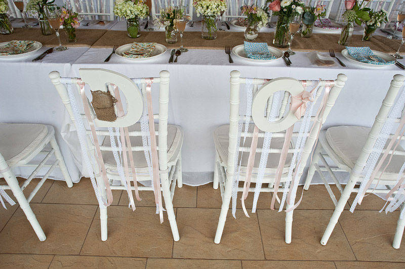 white bride and groom chair at wedding reception peach and white ribbons
