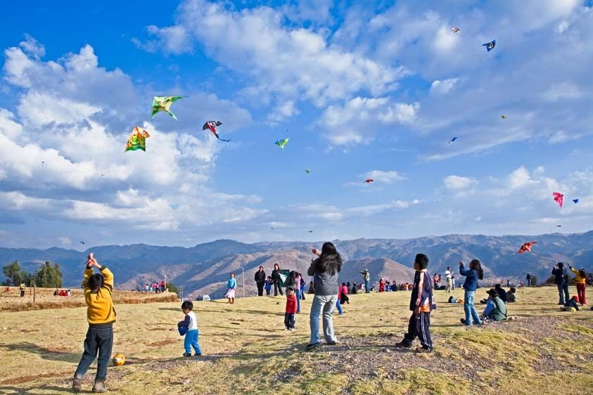 Children and families flying kites in Peru