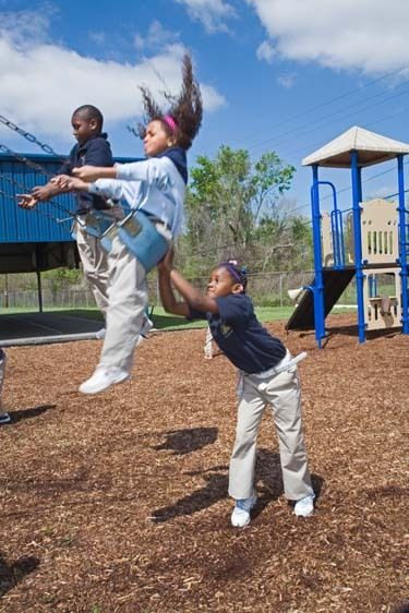 African American girl 7 years old pushes mixed black girl on swing