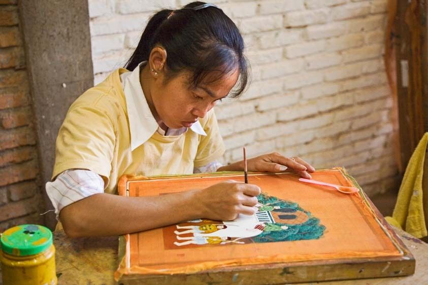 Cambodian young woman paints on silk