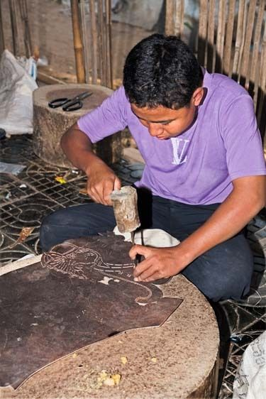 Cambodian boy carves elephant design in leather