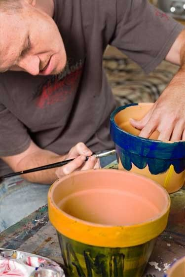 Young man of 20  yrs paints pot in class