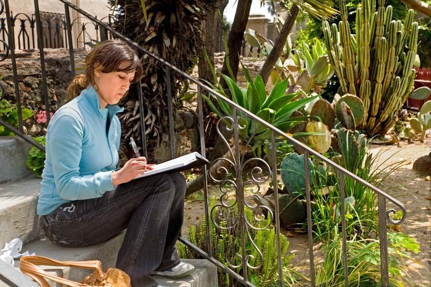 Young woman student in landscape drawing class sketches at mission outdoors