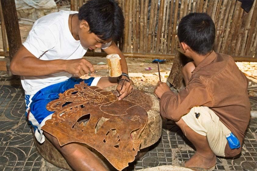 Cambodian young boy hammers design into leather