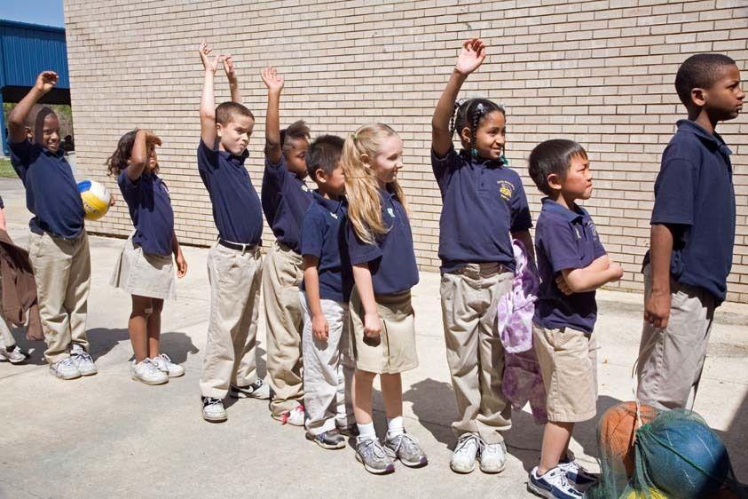Mixed race children in elementary school wait  in line at school