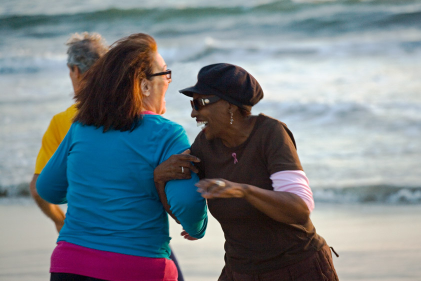 SR-0001_Two senior women dance on the beach with class at sunset