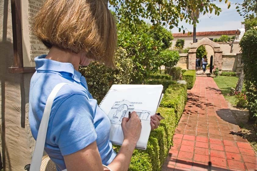 Female adult student sketches gate at San Gabriel Mission for cl