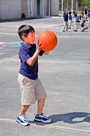 Vietnamese 7  boy aims basketball at goal