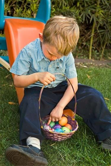 Little blonde headed boy of 3 and a half years old counts eggs in basket