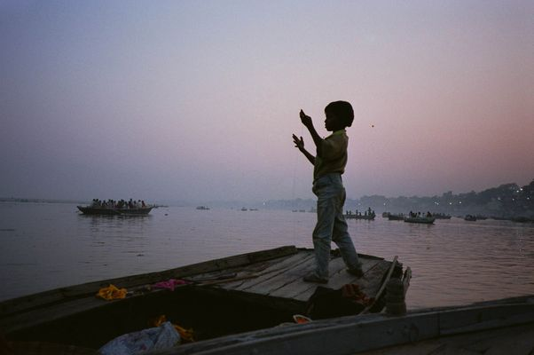 Boy fishing on the Ganges River, Varanasi, India