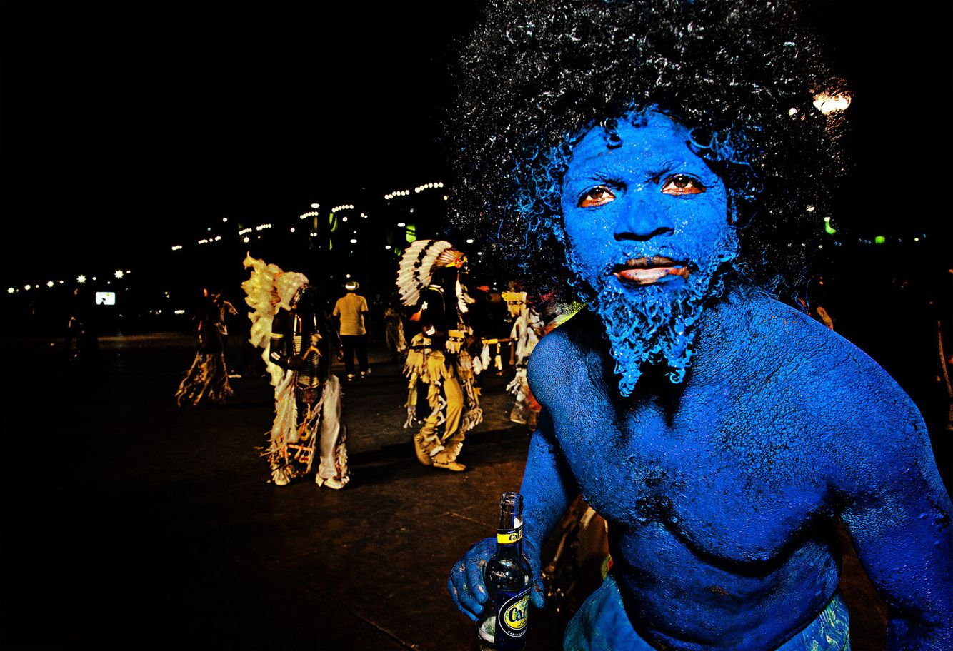 Iconic Traditional Carnival character: THE BLUE DEVIL with National Beer (Carib) in Hand.