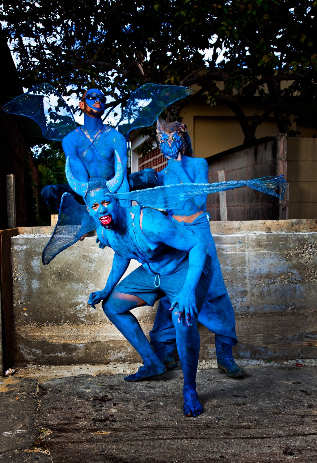 "A group of blue devils heckle bypassers with the saying of ""Pay de devil""."