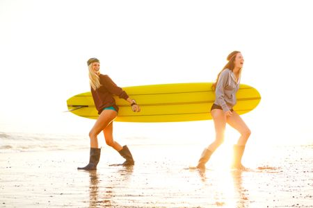 Surfer girls and yellow board