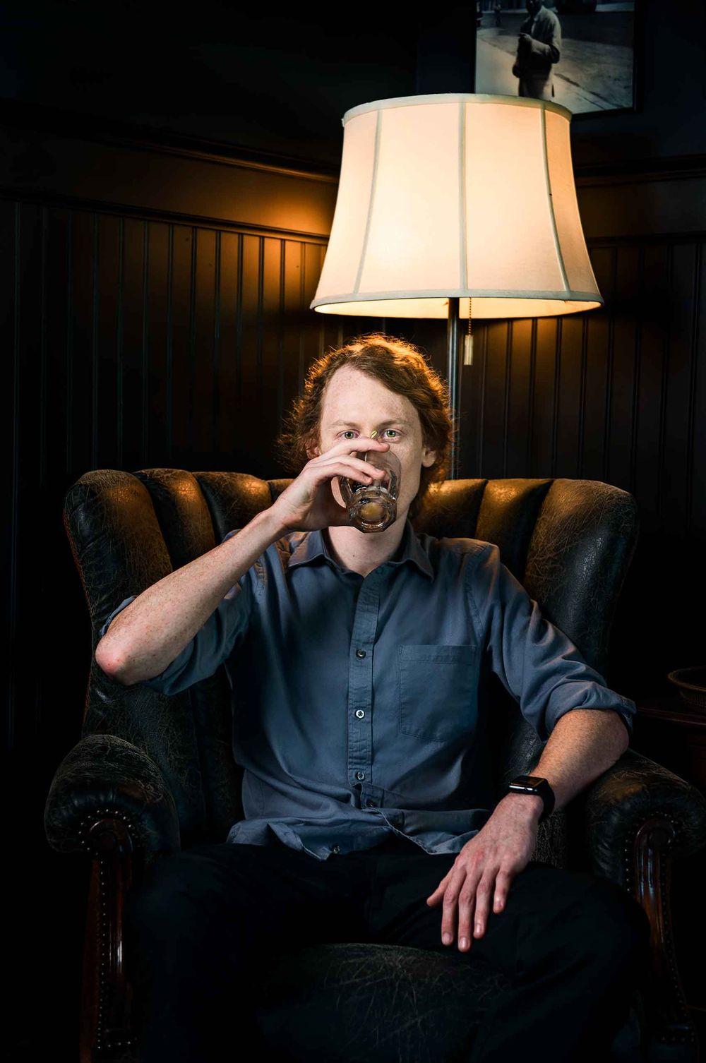 Man-drinking-cocktail-in-clubchair-TimCaffin-by-HenrikOlundPhotography.jpg