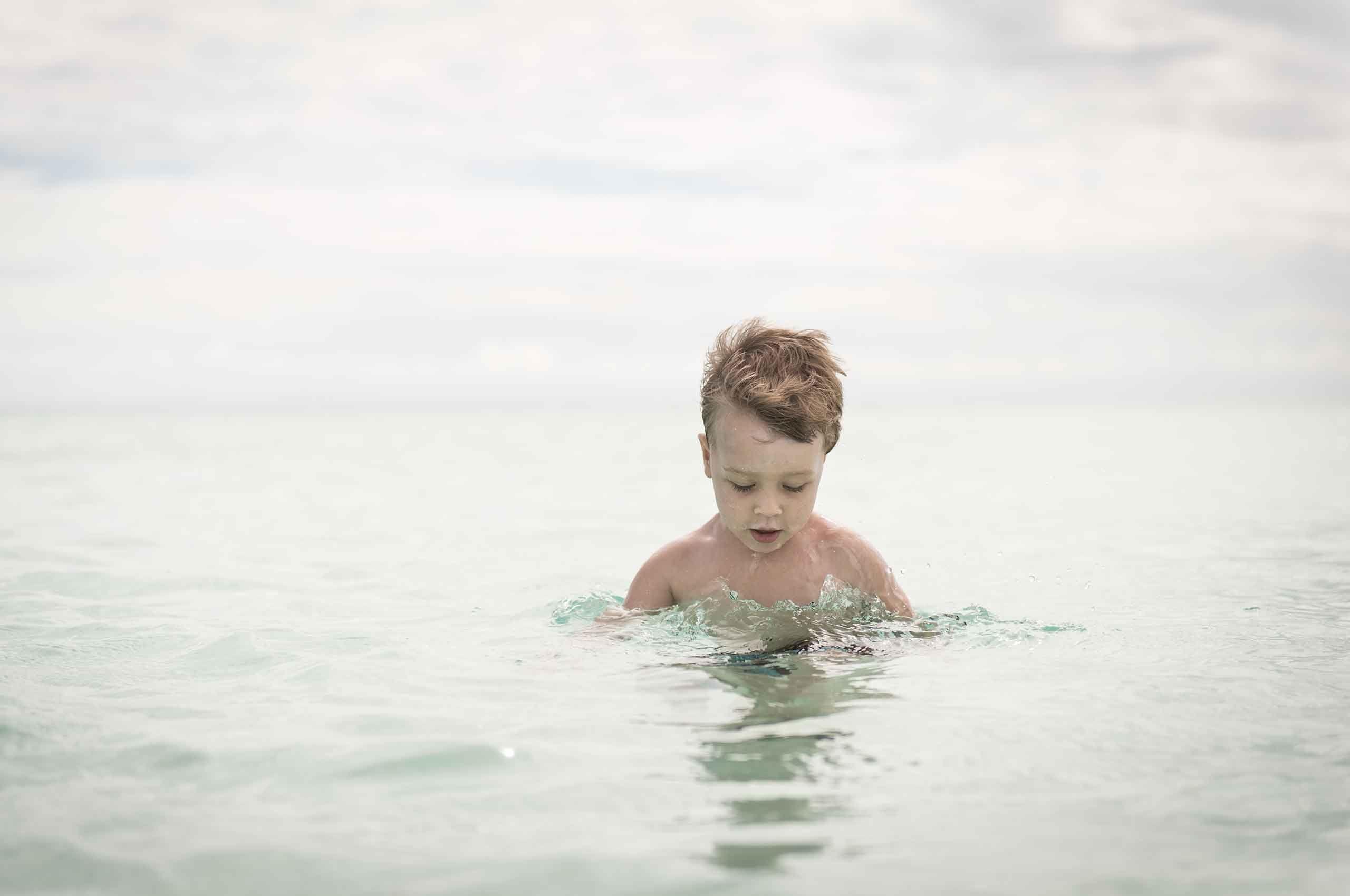 boy-standing-in-ocean-by-HenrikOlundPhotography.jpg