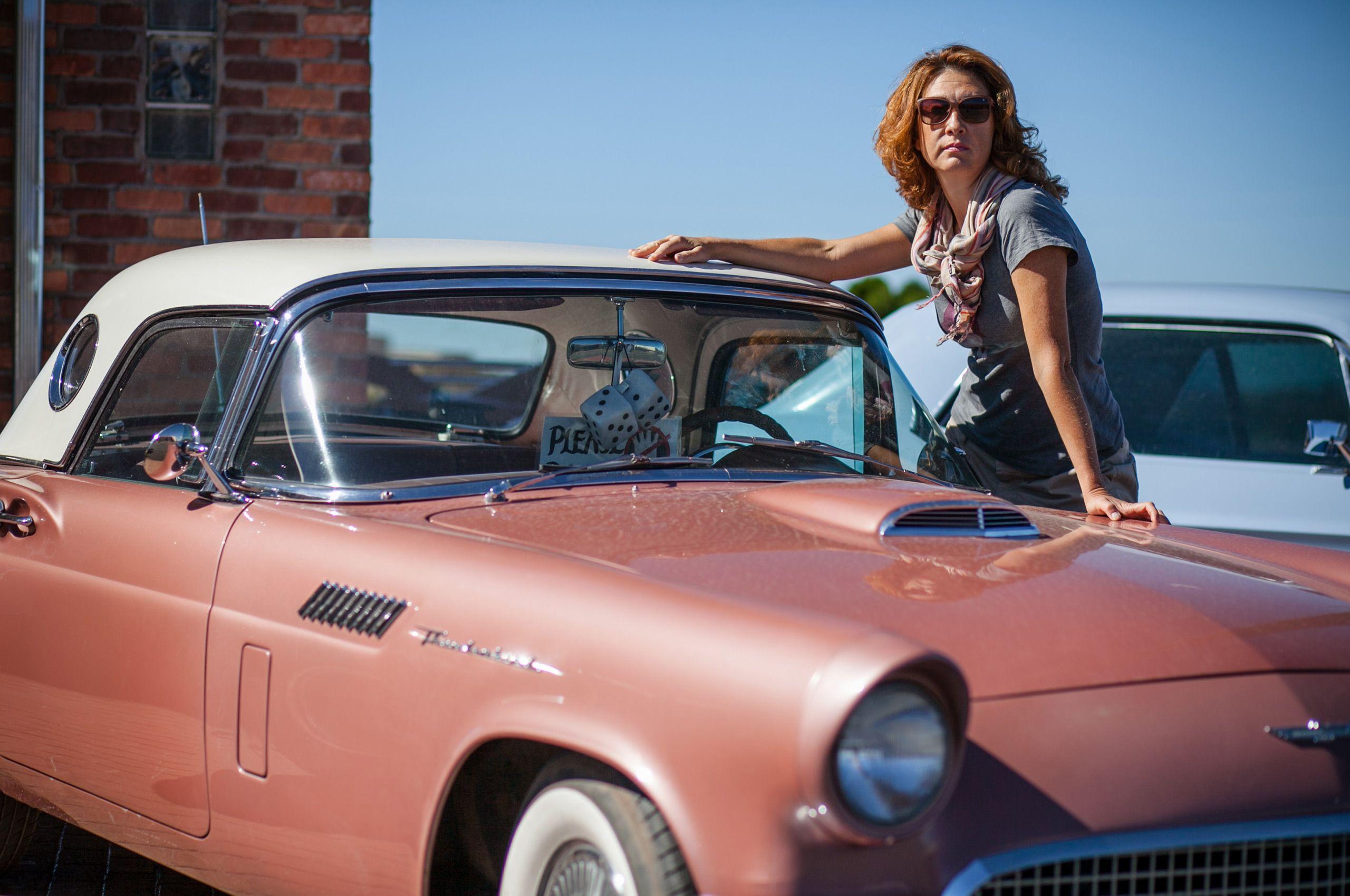 Beautiful lady staying near retro convertible