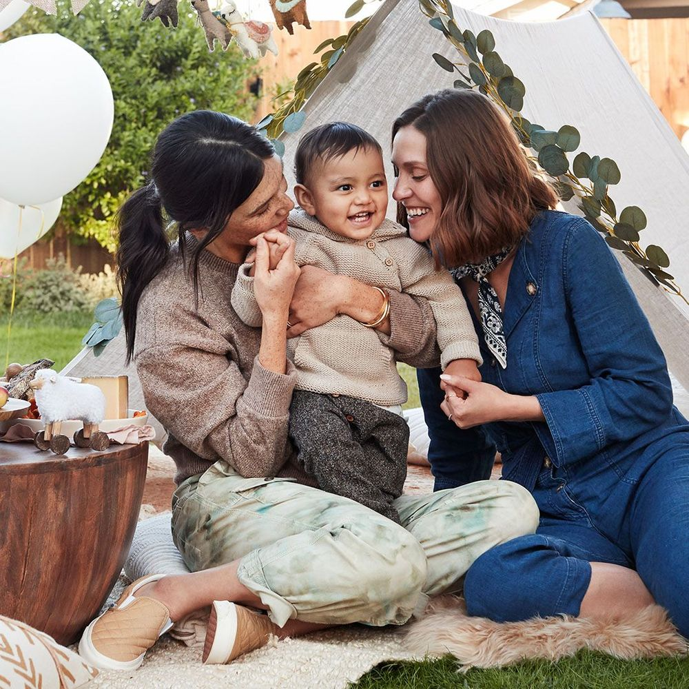 two moms holding baby at a birthday party