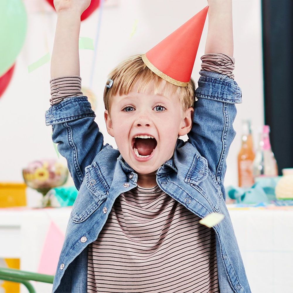 little boy with red birthday hat at a birthday party