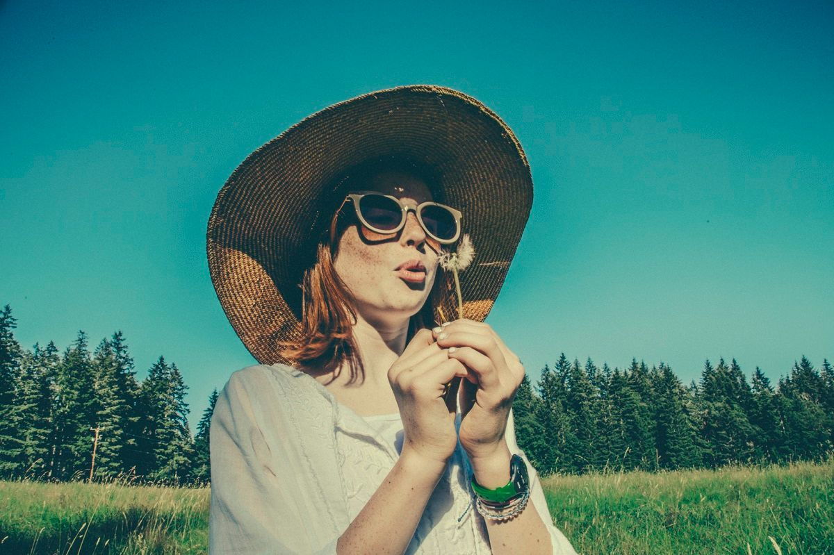 Woman In Hat Blowing On Dandelion By Seattle Lifestyle Photographer Alison Blomgren.