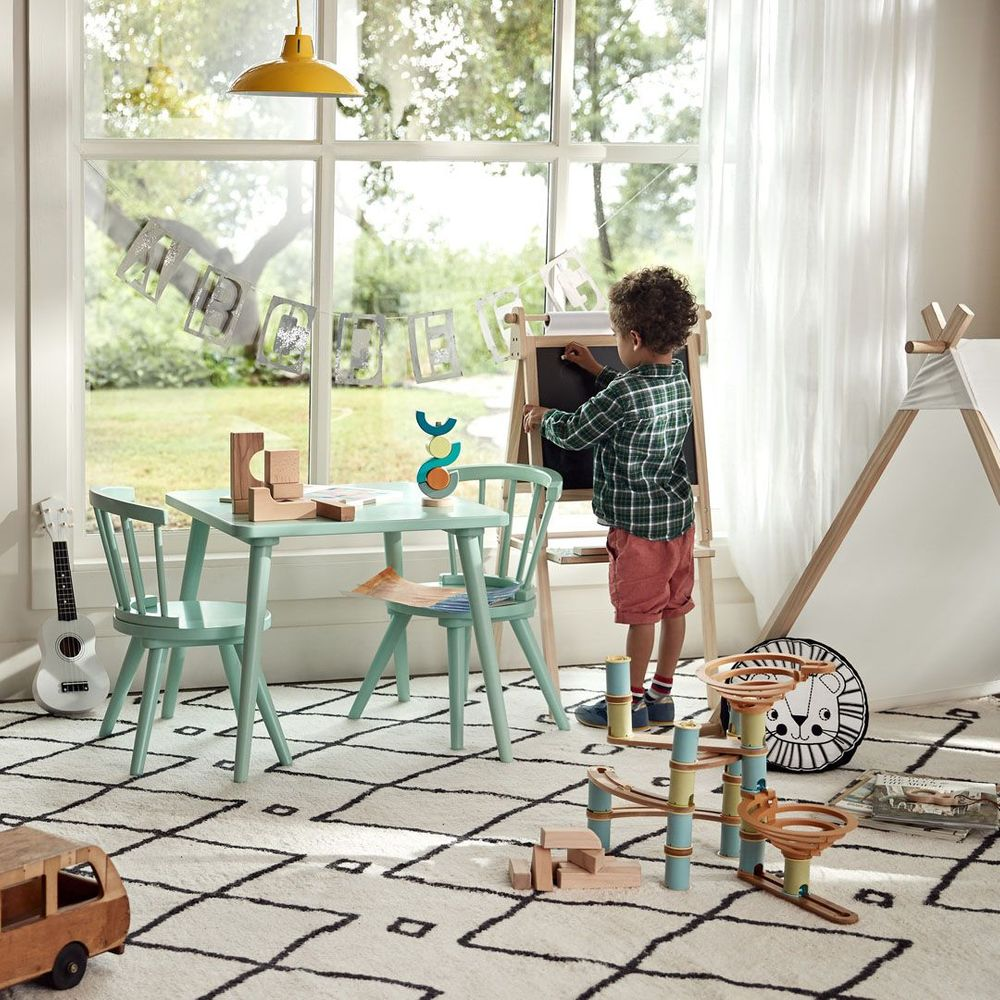 young boy playing with chalk board by window