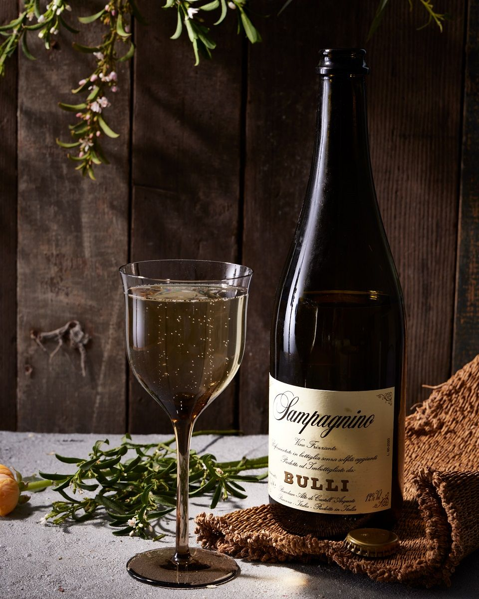 A glass of sparkling wine next to the bottle