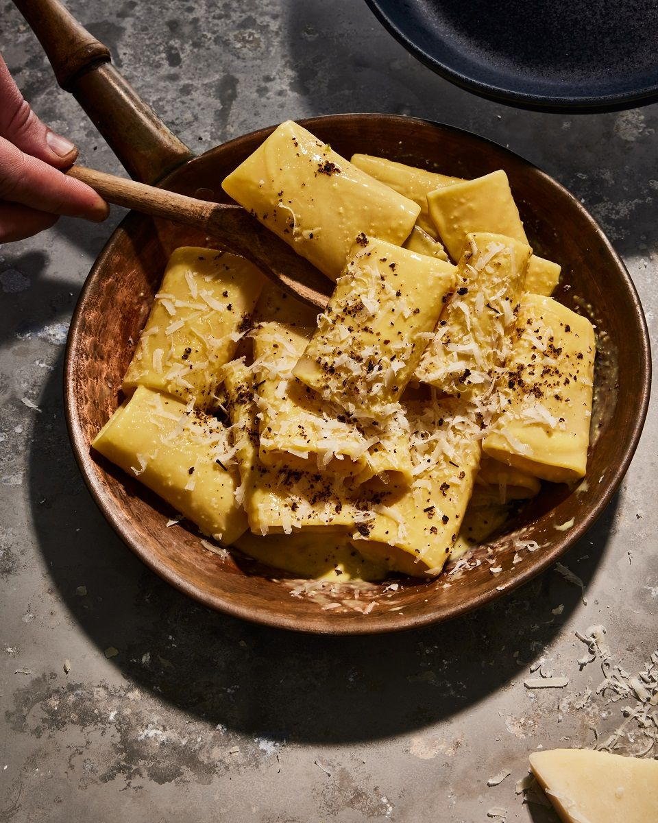 large, thick cut pasta noodles with cheese, sauce and pepper