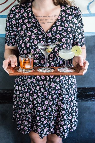 Lady holding trio cocktails