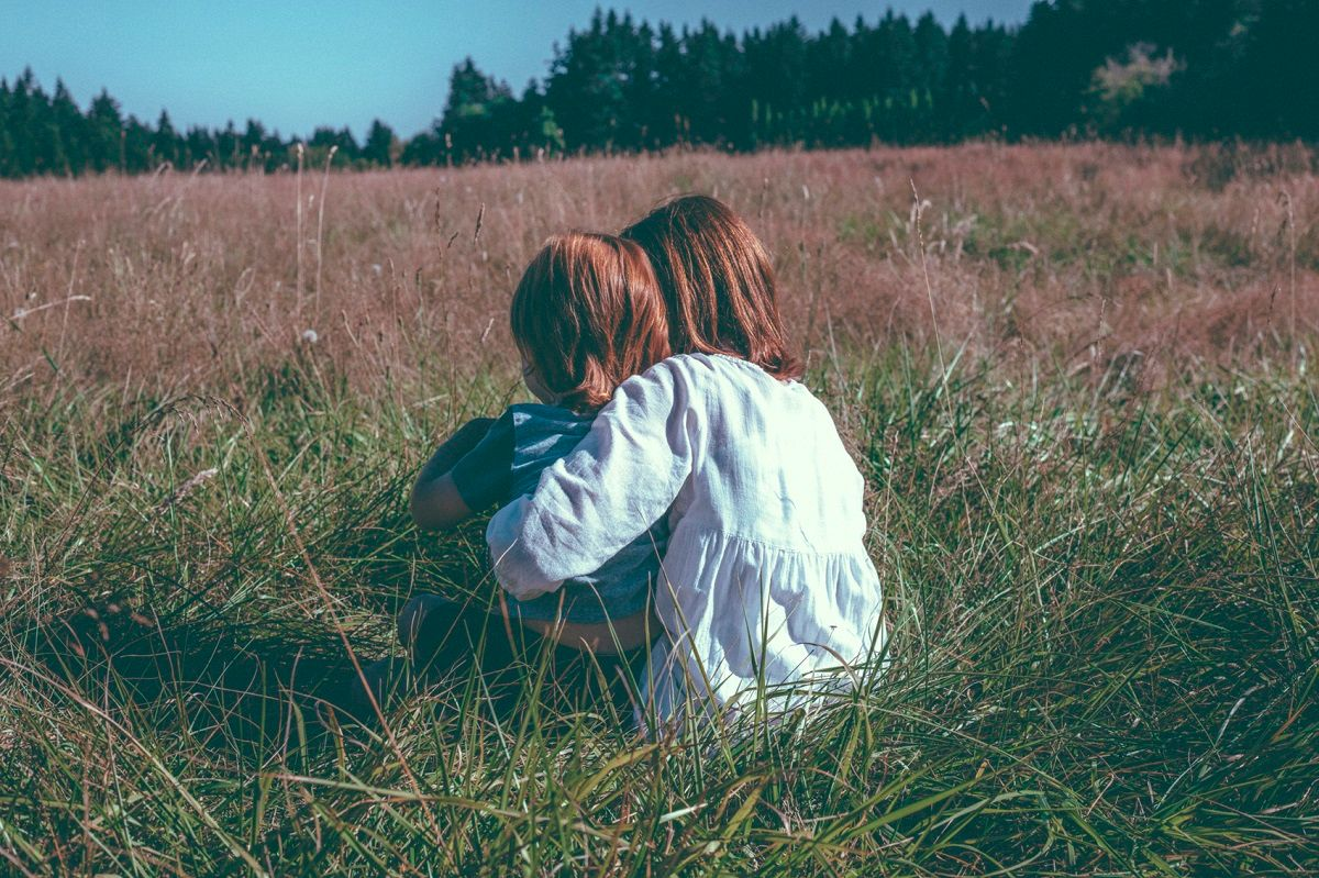 two redheads sitting in a field