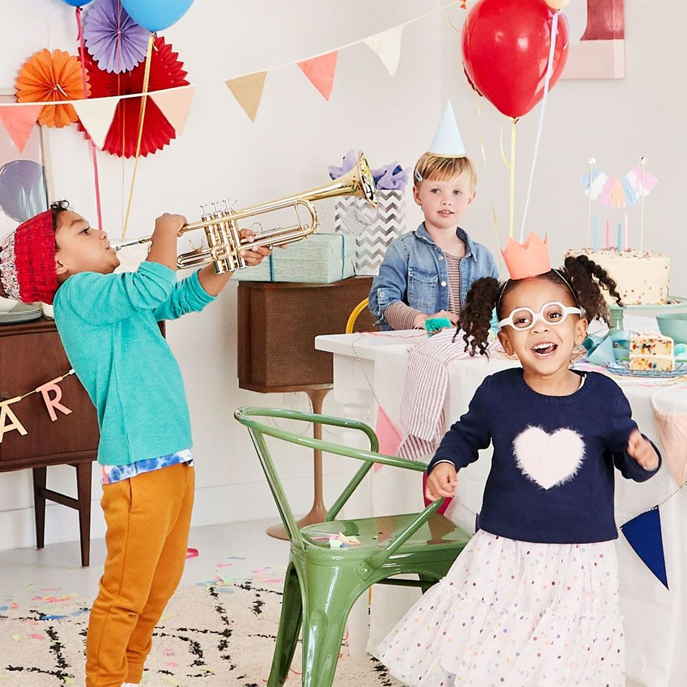 three kids celebrating around a table at a birthday party