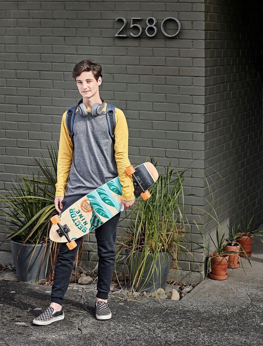 teenage boy holds skate board outside of house