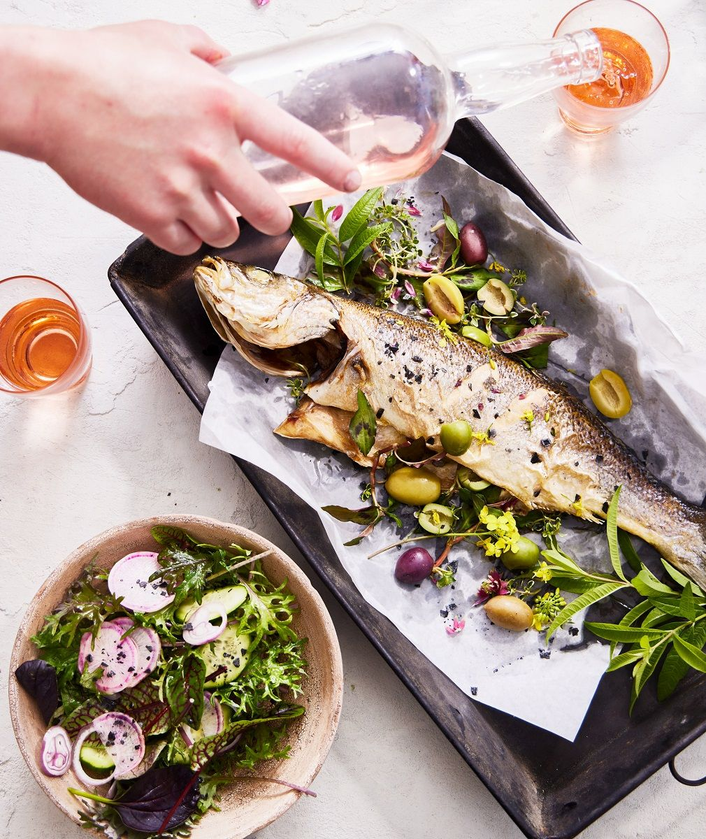 Grilled fish on a pan with salad and orange wine