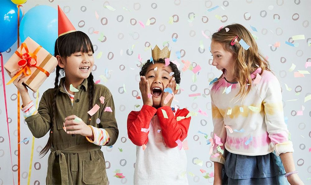 three kids in birthday hats laughing at a birthday party