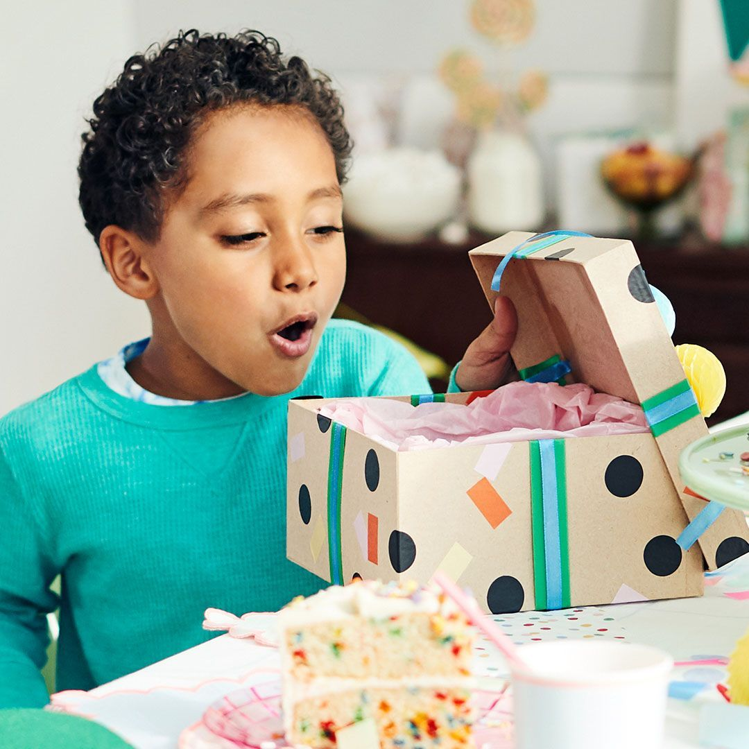 little boy opens a birthday present at a birthday party