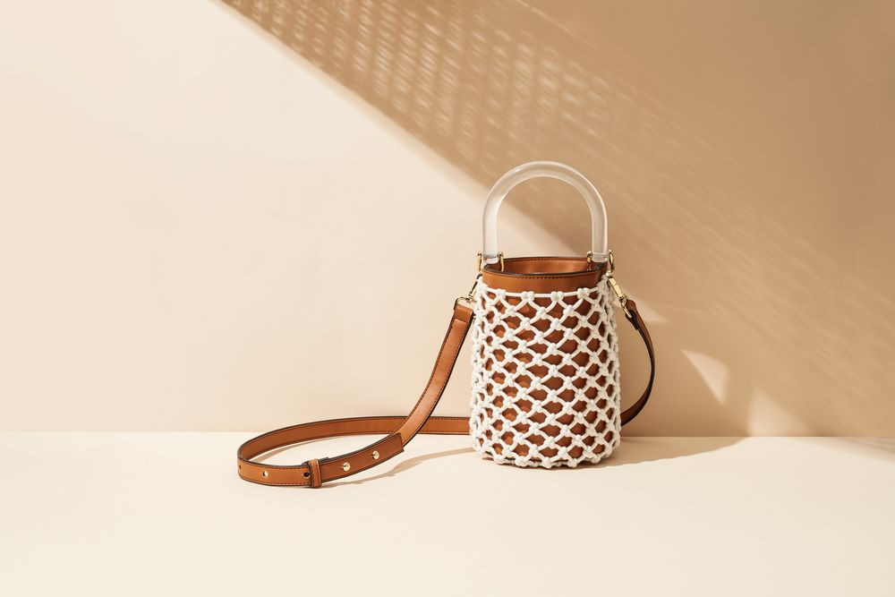 Lucite handle and leather bucket bag with netting